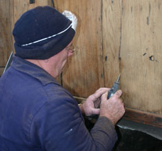 Trevor Bradshaw routing a crack in the external panelling ready for filling with a mix of cascamite and teak sawdust